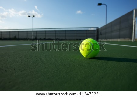 Tennis Ball on the Court with the Net Beyond