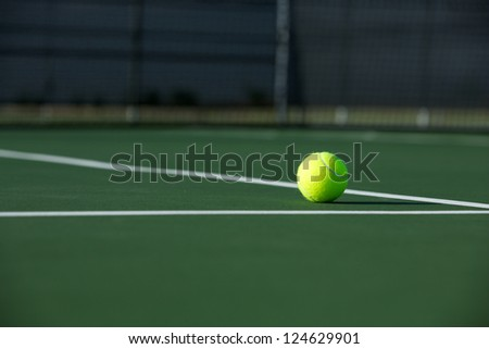 Tennis Ball on the Court with the Net Beyond - stock photo