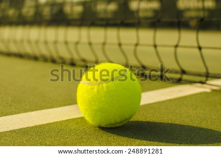 Tennis Ball on the Court with the Net in the background  - stock photo