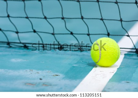 Tennis ball on the field. A mesh blocking out during the course.