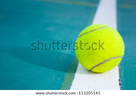 Tennis ball on the field. Tennis ball resting on a golf ball. - stock photo