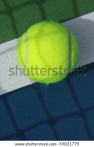 tennis ball on the inbound line on blue tennis field - stock photo