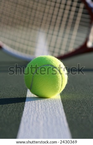 Tennis ball on the line with a racquet in the background - stock photo