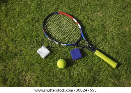 Tennis ball, racket and wristbands on grass field ground under sunlight - stock photo