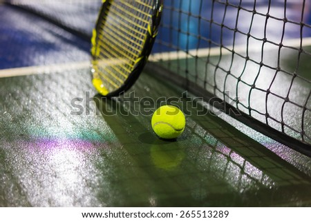 Tennis ball, racquet and net on wet ground after raining