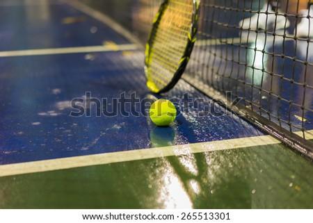 Tennis ball, racquet and net on wet ground after raining  - stock photo