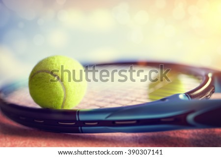 Tennis ball resting on top of a tennis racquet on a red asphalt court - stock photo