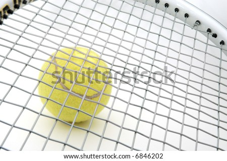 tennis ball under a racket. focus on ball. - stock photo