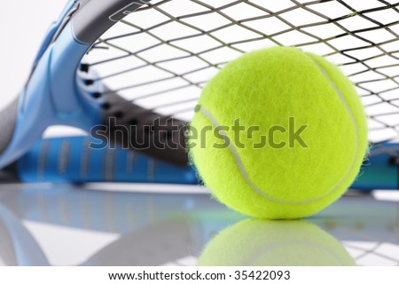 Tennis ball under the strings of a tennis racket - stock photo