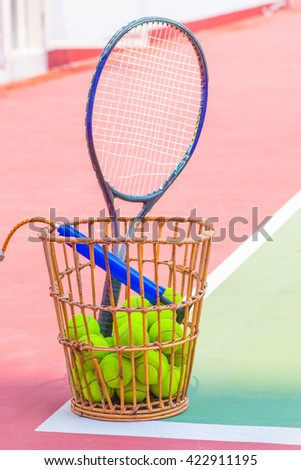 Tennis Ball with Racket on basket tennis court - stock photo
