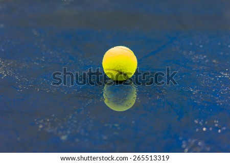 Tennis ball with reflection on ground after raining - stock photo