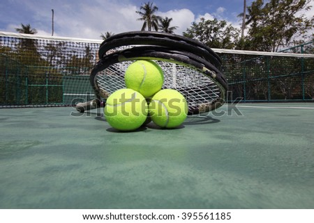 Tennis balls and racket on court close up - stock photo