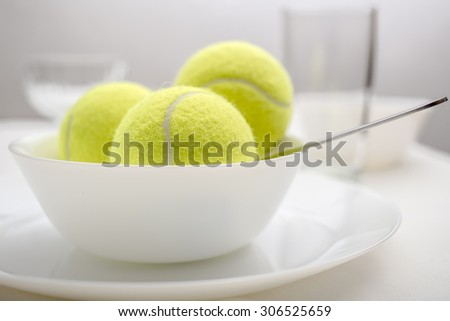 Tennis balls are in a bowl instead of ice cream, symbolizing changes and refusal of desserts and sweet and replacement of sports and healthy lifestyle. White variant. - stock photo