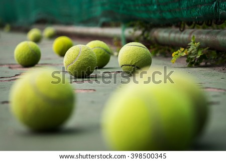 Tennis balls in old court - stock photo