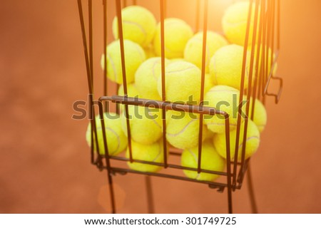 Tennis balls in the basket on the background of the tennis court - stock photo
