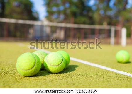 tennis balls lying on the court - stock photo