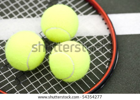 Tennis balls on a racket on the court ground