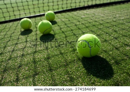tennis balls on tennis grass court - stock photo