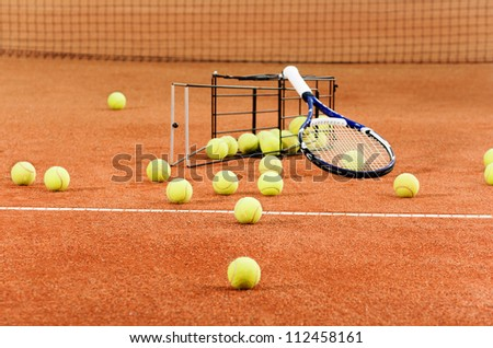 Tennis balls scattered from basket on court - stock photo