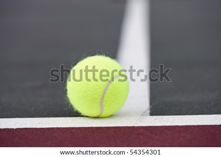 Tennis balls sitting on the ground at a tennis court