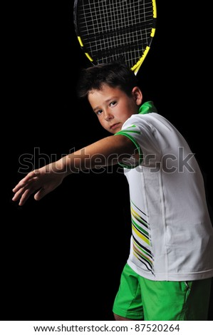 Tennis boy playing forehand isolated in black - stock photo
