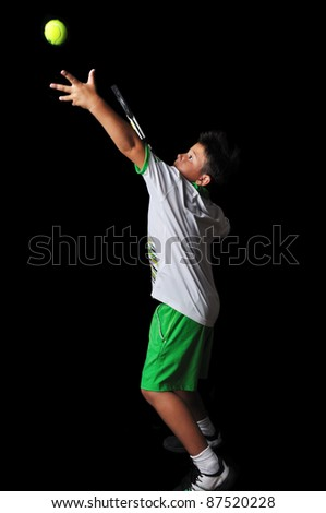 Tennis boy serving isolated in black - stock photo