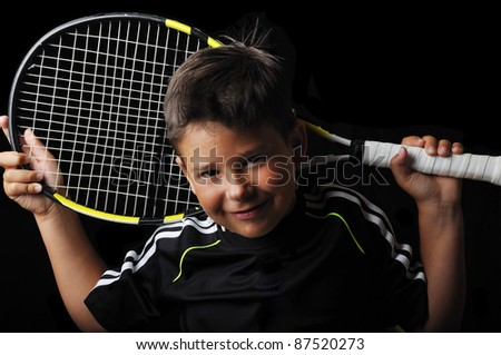 Tennis boy smiling isolated in black - stock photo