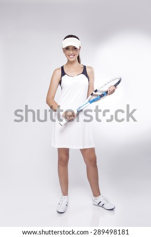 Tennis Concept and Ideas: Full Length of Female Professional Tennis Player in Studio. Holding Tennis Racket In Front. Vertical Image Composition - stock photo