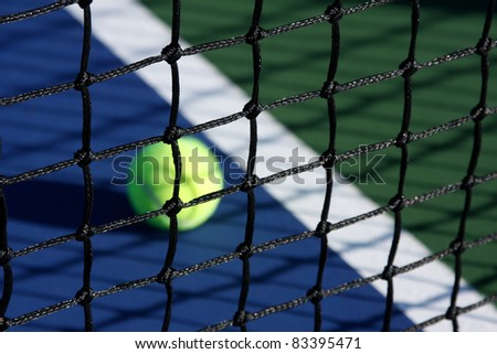 Tennis Court Net close up with the ball and court in background