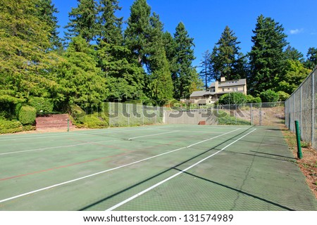 Tennis court with Large brown house exterior with summer garden. Northwest.