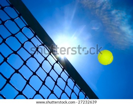 Tennis game concept with ball flying over the net under the blue sky. - stock photo