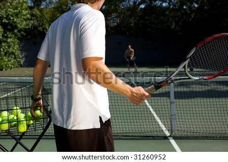 Tennis Instructor Teaching His Student - stock photo