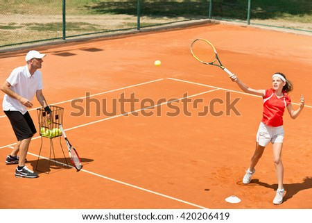 Tennis instructor working with student - practicing volleys - stock photo