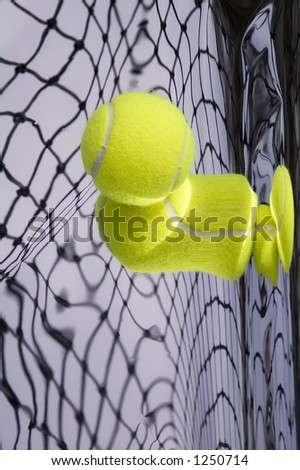 Tennis net and yellow ball with warped reflections - stock photo
