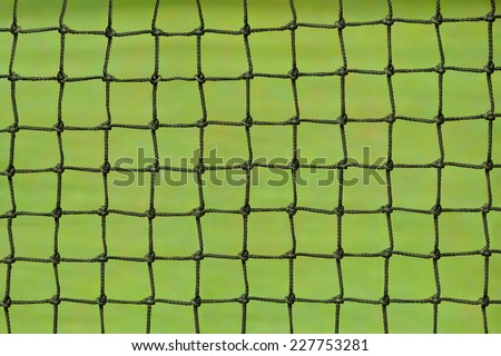 Tennis net on a green grass court. - stock photo