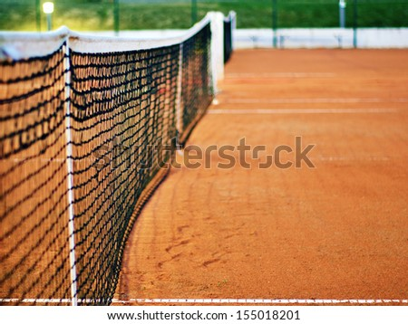Tennis net on red clay court. Night show with shallow depth of field - stock photo