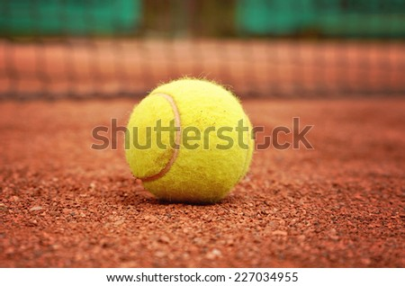 Tennis net with fast tennis ball on clay court