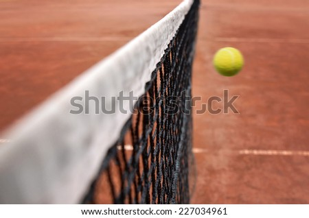Tennis net with fast tennis ball on clay court - stock photo
