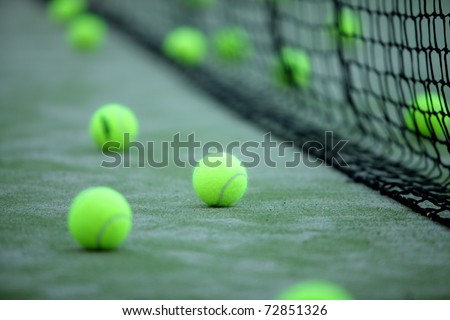 Tennis or paddle balls on synthetic grass of paddle court with net on the background - stock photo