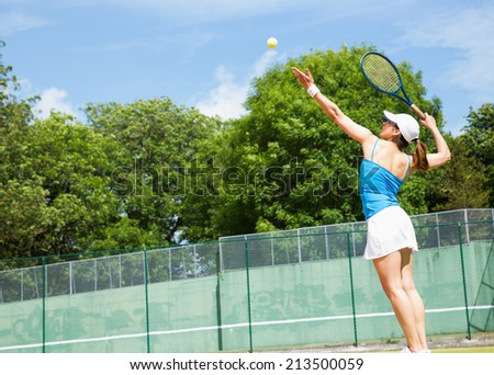 Tennis player about to serve on a sunny day - stock photo