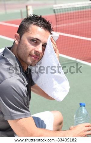Tennis player drying head - stock photo