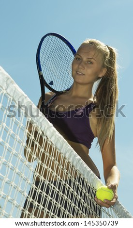 tennis player girl standing at net and smiling - stock photo