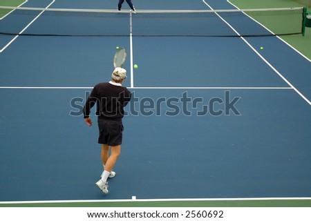 Tennis player hitting ball - stock photo
