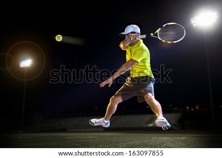 Tennis player hitting the ball at night - stock photo