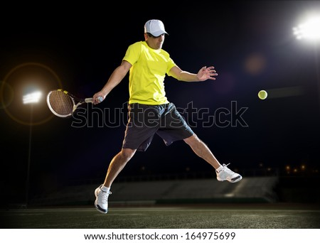 Tennis player hitting the ball during a match at night - stock photo