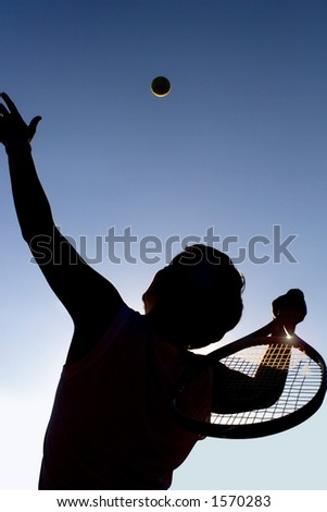 Tennis player on the field, serving the ball. Nice countre-jour light!