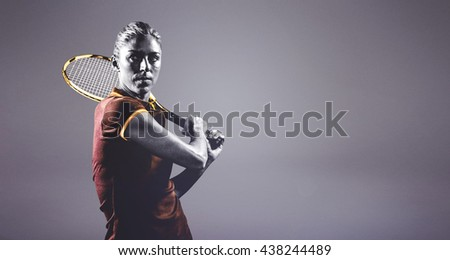 Tennis player playing tennis with a racket against grey background