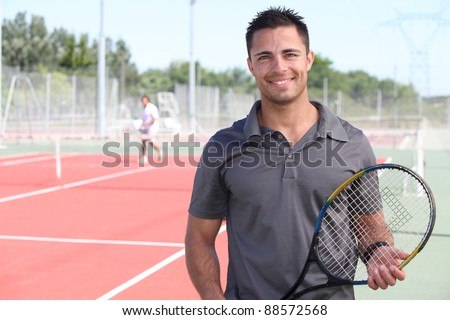 tennis player posing in front of a tennis court - stock photo