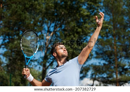Tennis player serving ball. Low angle view of confident male tennis player serving a ball - stock photo
