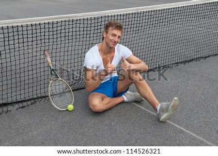 Tennis player sitting besides the net and showing thumbs up.